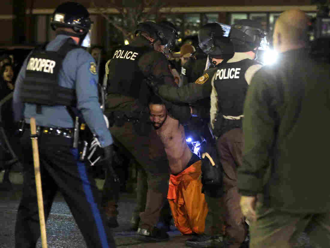 A man is arrested by police after kneeling in the street during a protest outside the Ferguson Police Department on Saturday.