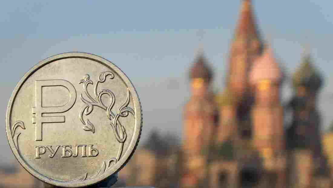A Russian ruble coin is pictured in front of St. Basil cathedral in central Moscow, on November 20, 2014.