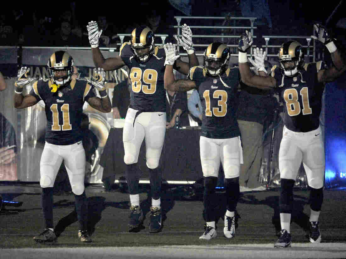 "Members of the St. Louis Rams raise their arms in a ""hands up, don't shoot"" pose as they walk onto the field before an NFL football game against the Oakland Raiders."