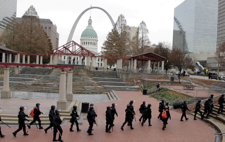 Officers wearing riot gear walk through a park in downtown St. Louis on Sunday. (Tom Gannam/AP)
