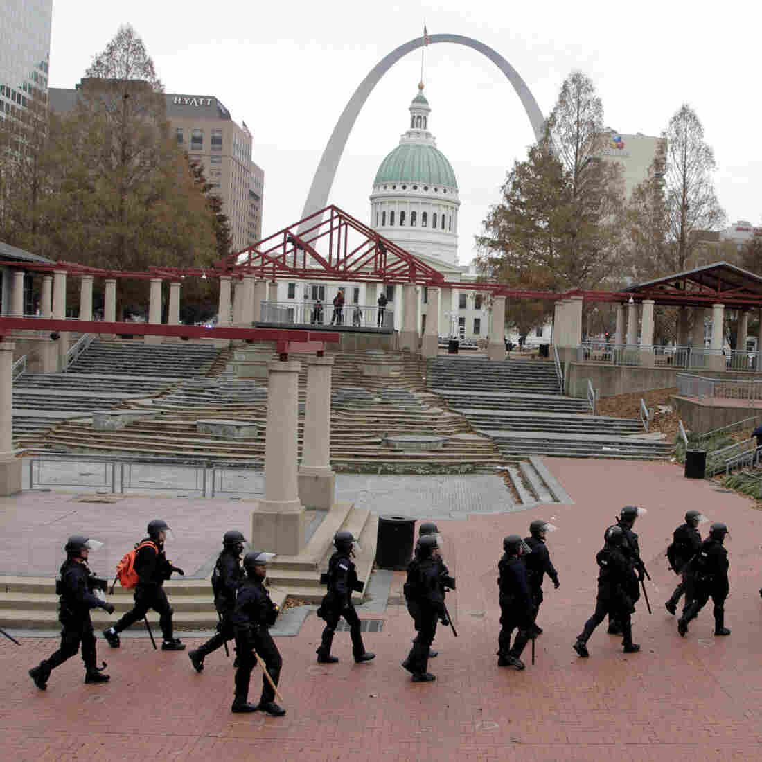 Officers wearing riot gear walk through a park in downtown St. Louis on Sunday.
