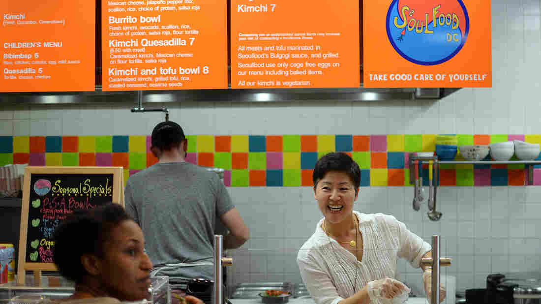 "Anna Goree (right) talks to customer Tioni Collins while Anna's husband, Jon Goree, prepares the food at Seoul Food D.C. restaurant, which is located inside an Exxon gas station. ""My wife Anna is not only an excellent cook; she knows everyone by name and has good rapport with our customers,"" Jon tells The Salt."