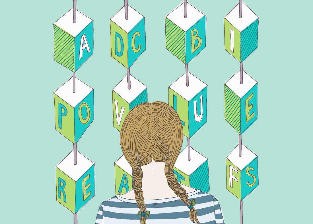 Girl looking at alphabet blocks --- Image by © Trina Dalziel/Ikon Images/Corbis
