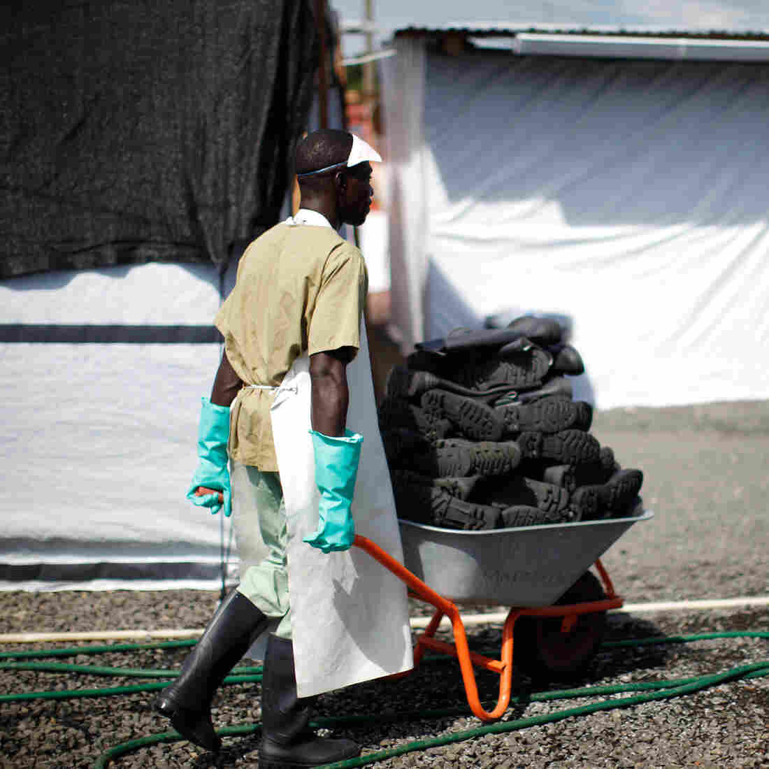A health care worker wheels a stack of freshly washed boots to ELWA 3 Ebola treatment unit in Monrovia, Liberia.