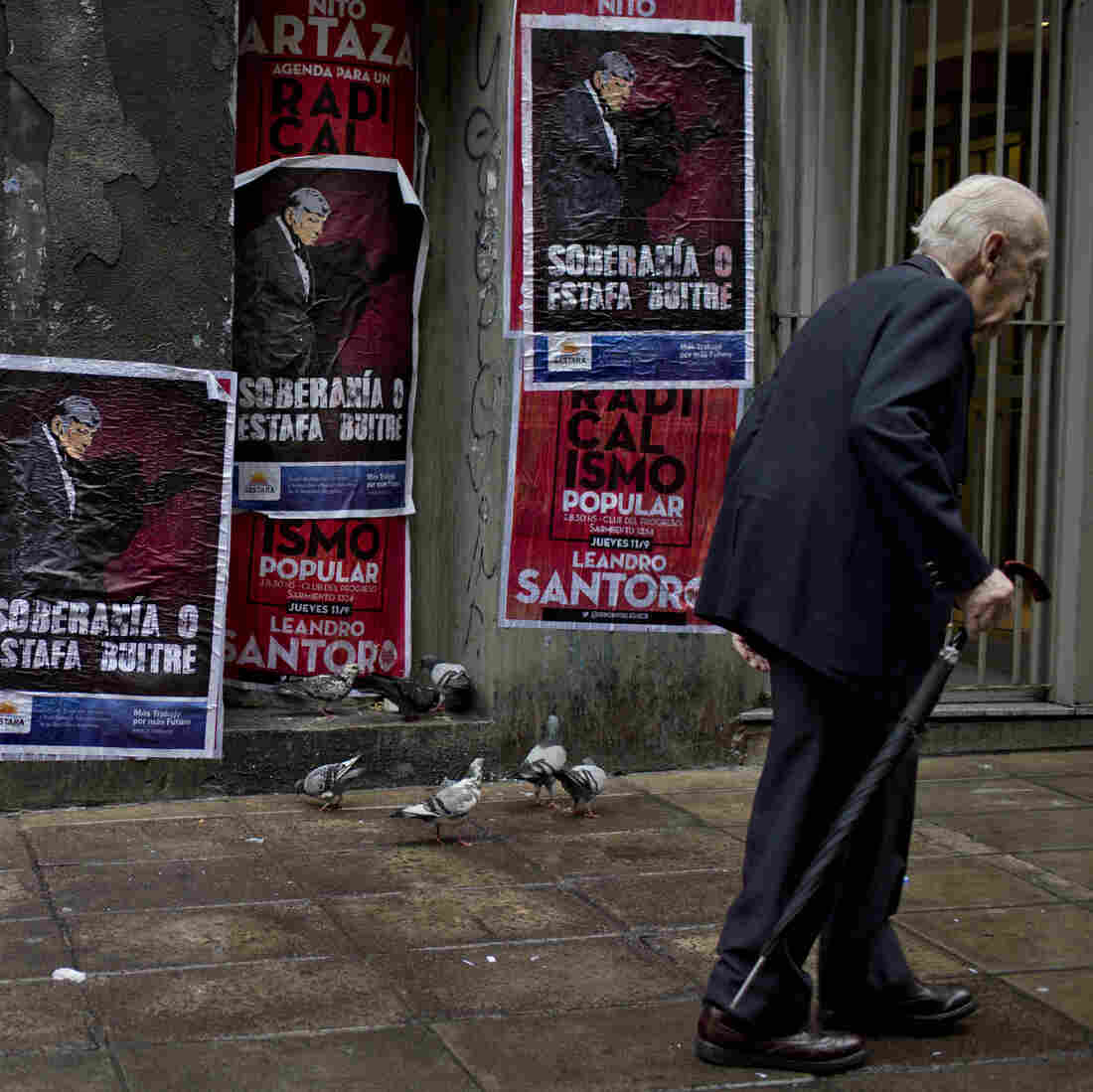 """A wall in Buenos Aires, Argentina, displays posters with an image of U.S. Judge Thomas Griesa and a message in Spanish — """"Sovereignty or vulture scam"""" — in support of Argentina's government in its dispute against a U.S. hedge fund, known locally as a """"vulture fund."""""""