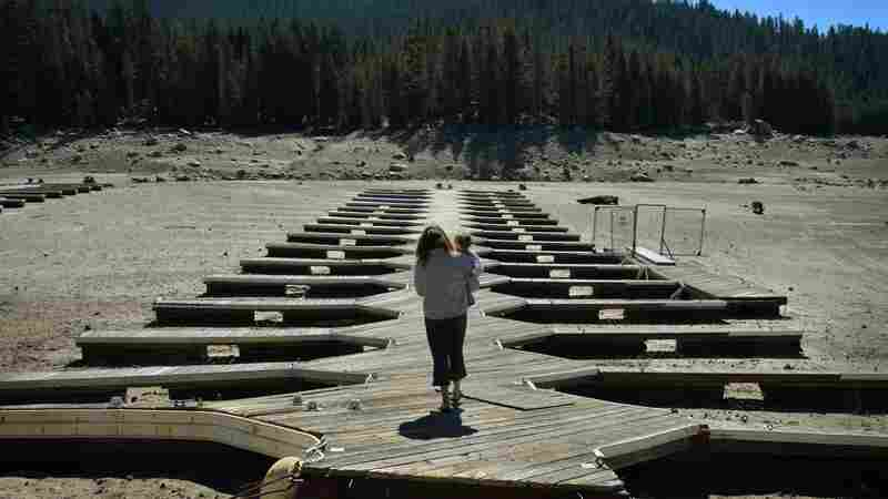 Marina owner Mitzi Richards carries her granddaughter in September as they walk on their boat dock at the dried up lake bed of Huntington Lake in California, which was at only 30 percent capacity as