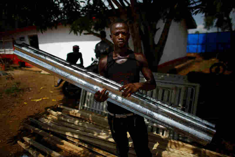 A worker helps to build an addition onto an Ebola holding center in the Port Loko district of Sierra Leone.