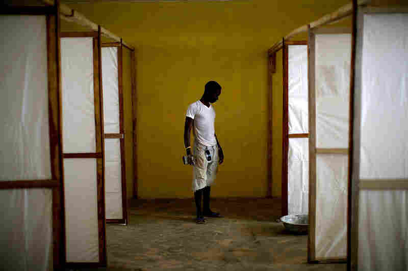 A worker puts the finishing touches on the dividers that will separate patients at the community care center in the Port Loko district of Sierra Leone.