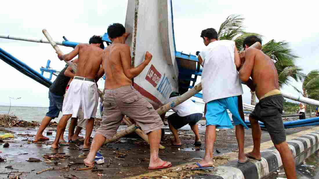 Fishermen carry their outrigger to higher ground Friday in Legazpi City, south of Manila.