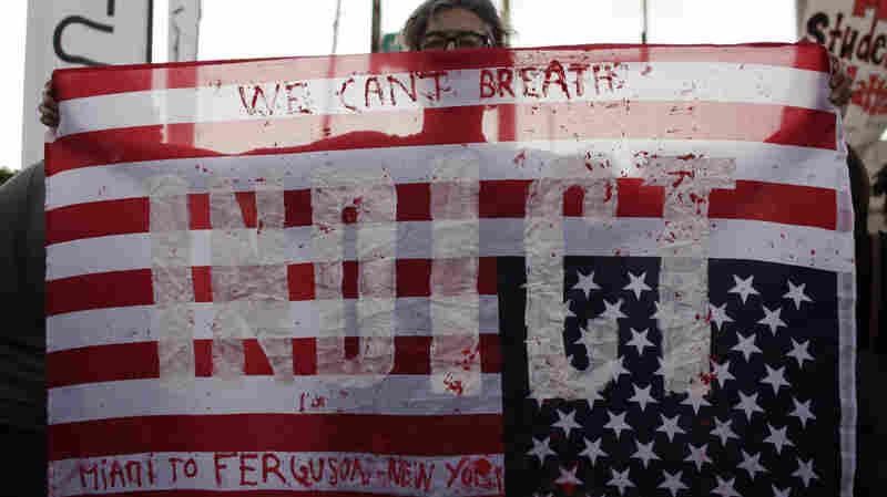 """A protester holds an American flag with the word """"Indict"""" painted on it Friday during a protest in Miami."""