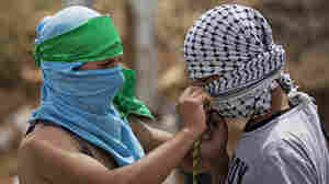 A Palestinian with a green headband, which identifies him as a Hamas supporters, helps a fellow protester with a black-and-white scarf, the symbol of the Fatah movement. They were both taking part in a demonstration near the West Bank city of Ramallah on June 4. The factions agreed to end their feud earlier this year, but many of their supporters remain bitter rivals.