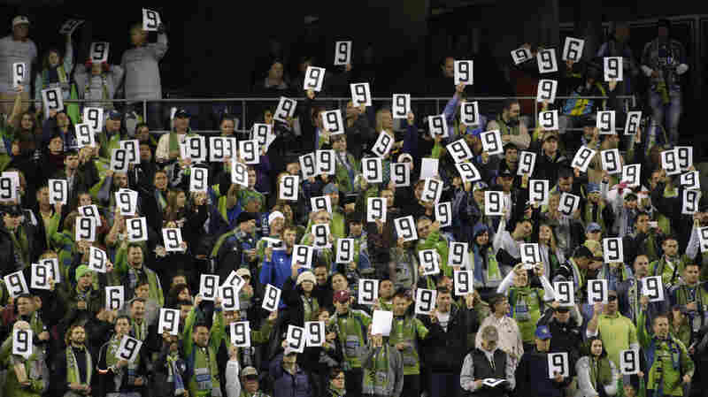 Fans at Qwest Field in Seattle hold up the number nine, Davies' number, near the ninth minute of a match between the Seattle Sounders FC and FC Dallas in 2009. The crowd was honoring Davies, who had been seriously injured in a car accident.