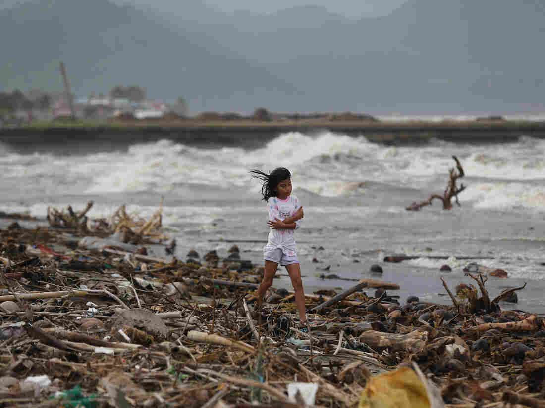 A girl walks along the shore as strong waves from Typhoon Hagupit hit Atimonan, Quezon province, eastern Philippines on Saturday.