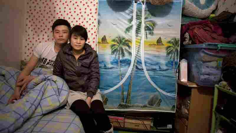 Zhuang Qiuli and her boyfriend Feng Tao sit on the bed in their basement apartment two floors below a posh condominium. Since this photo was taken, the couple has moved above ground.
