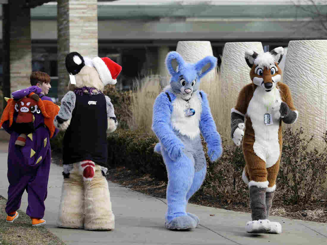 Frederic Cesbron (right) and Maxim Durand walk on the street outside the Hyatt Regency O'Hare hotel in Rosemont, Ill., on Sunday. Thousands of people were evacuated earlier after a chlorine gas leak at the hotel, which is hosting the 2014 Midwest FurFest convention.