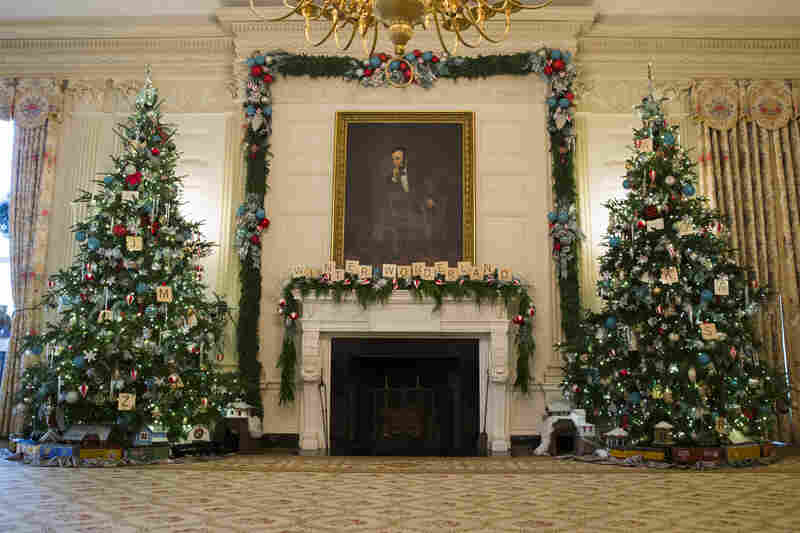 Christmas trees flank the fireplace in the East Room of the White House. Every year, about 100 volunteers decorate the White House with garlands, ribbons and lights.