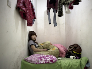Twenty-one-year-old Liu Jing sits in her apartment two stories underground Beijing, China. Her laundry hangs above her head because there's nowhere else to put her clothes.