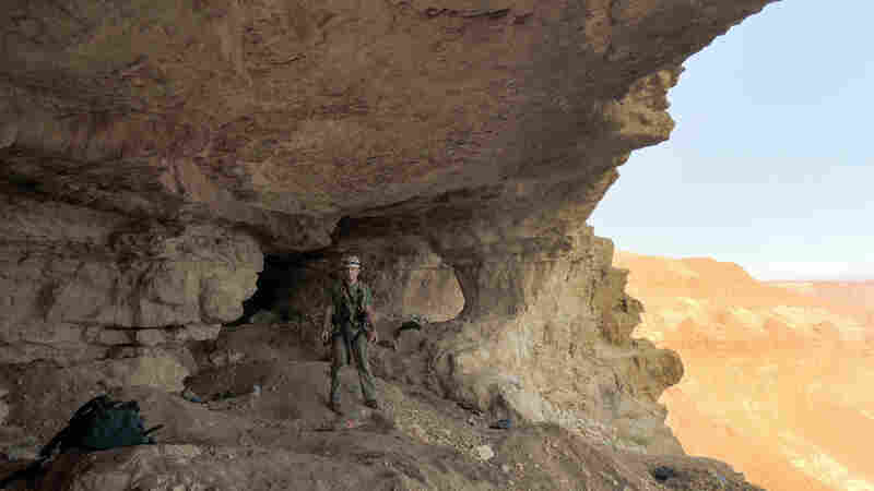 An Israeli Antiquities Authority Prevention of Antiquities Robbery officer stands at the opening to a high cave in the Judean desert. Six men were indicted Sunday for looting from this cave.