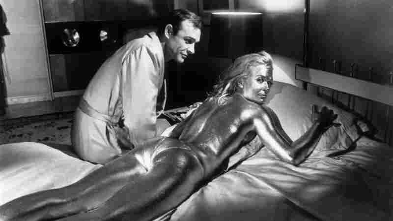 Sean Connery sits beside his co-star, English actress Shirley Eaton, covered in gold, during the filming of a scene from Goldfinger in 1964.