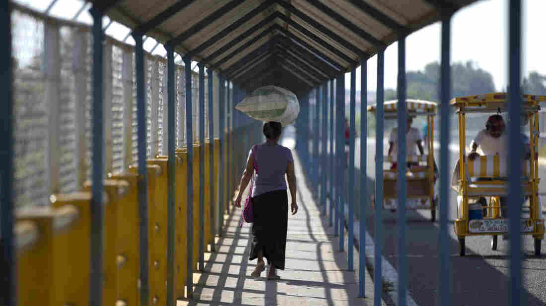 A woman walks on a Suchiate River bridge connecting Guatemala and Mexico. A State Department program allows some immigrants to bring their children to the U.S. from Honduras, El Salvador and Guatemala.