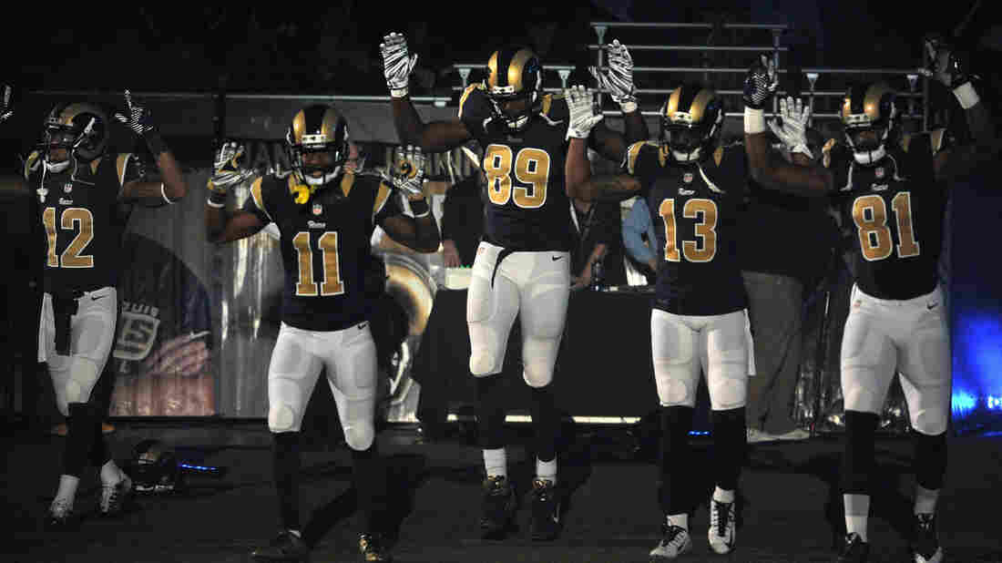 Members of the St. Louis Rams raise their arms to protest the grand jury decision in Ferguson, Mo., before a game last month. The players faced a backlash from St. Louis police and have been asked to apologize.