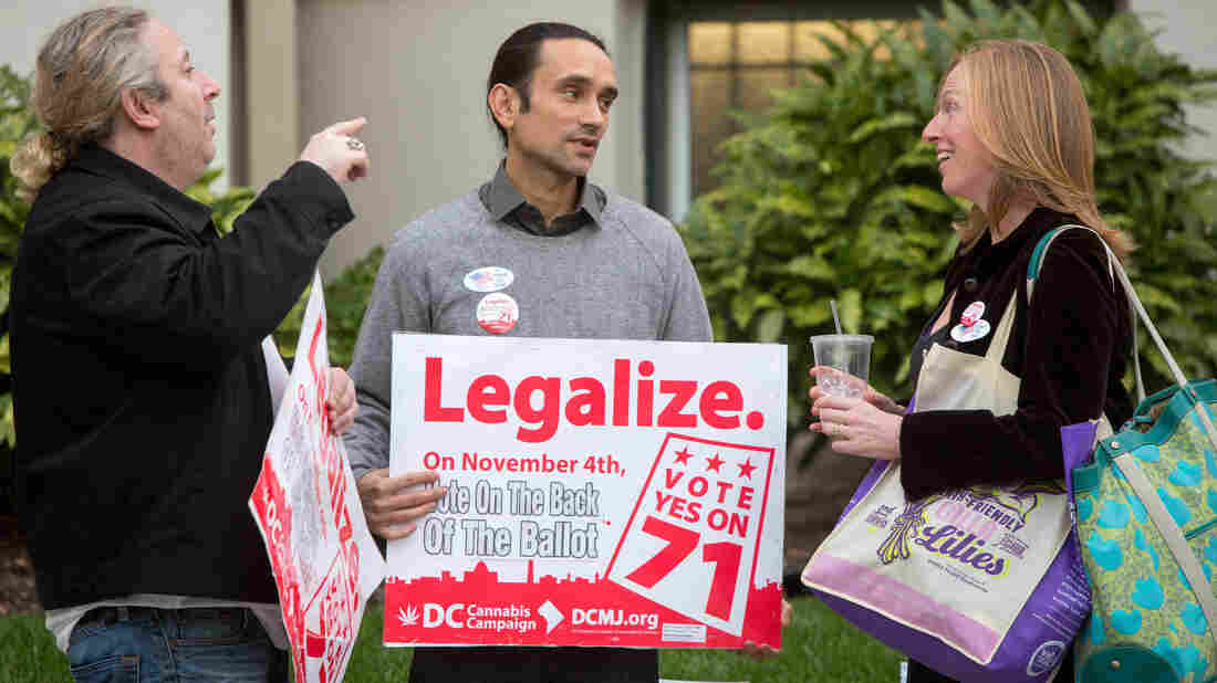 Volunteers with the DC Cannabis Campaign (left and center) talk to a voter on Election Day about the ballot initiative to legalize marijuana. The measure was approved, but its fate remains uncertain.