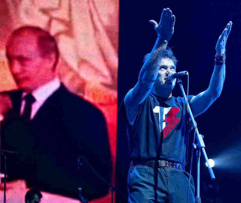 """The Russian pop group Televizor has criticized Russia's involvement in Ukraine. Here, frontman Mikhail Borzykin performs at a 2011 show in St. Petersburg. At some concerts he sings, """"Putin is a fascist,"""" a reference to the Russian president, shown on the screen behind him."""