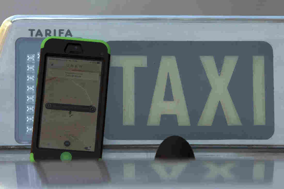 The Uber smartphone app is seen next to a taxi sign in Madrid, Spain. A Spanish judge this week ordered Uber to cease operations in the country. It's among the latest challenges facing the ride-sharing service recently valued at $40 billion.