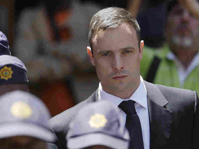 Oscar Pistorius is escorted by police officers as he leaves the high court in Pretoria, South Africa, on Oct. 17. A South African judge ruled today that prosecutors can appeal the culpable homicide verdict handed to the athlete for killing his girlfriend Reeva Steenkamp.