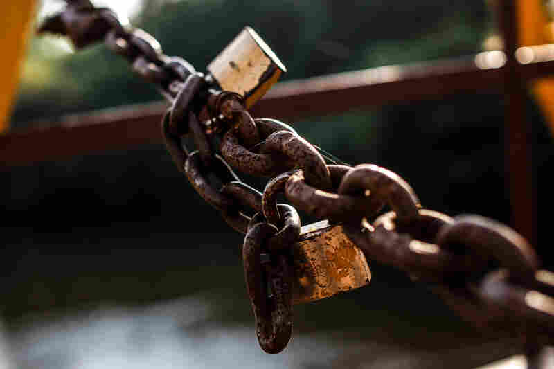 A large rusty chain across the bridge, with two padlocks, marks where Liberian territory ends. There's a similar chain on the Guinean side.