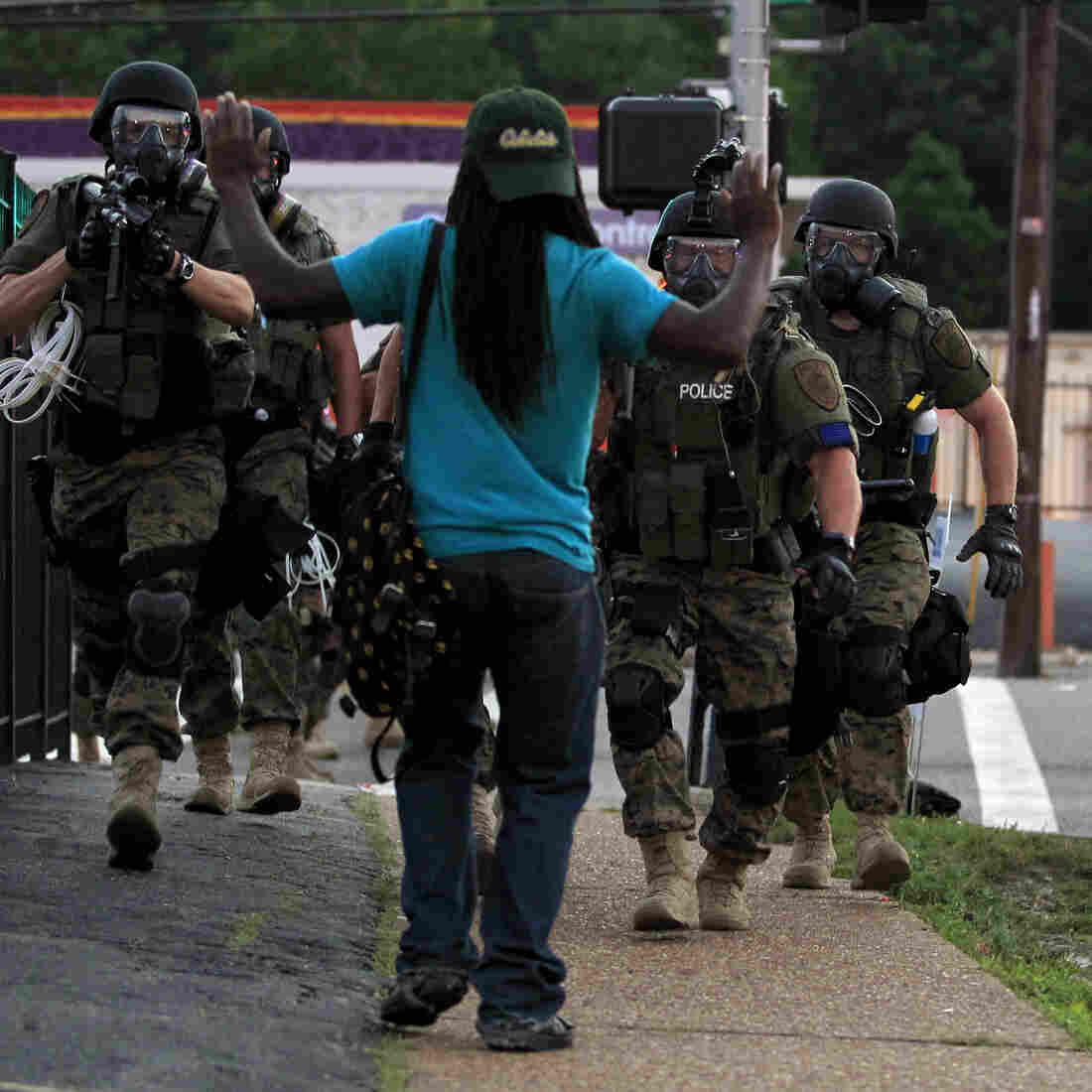 Police wearing riot gear walk toward a man with his hands raised Aug. 11 in Ferguson, Mo. Renewed calls for police departments to hire more minorities have followed the shooting there of a black man by a white police officer.