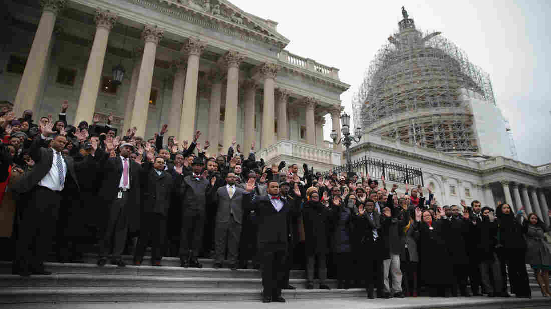 Black congressional staffers hold their hands up as they pose for a group photo during a walkout on on the steps of the U.S. Capitol Thursday, in a protest over the Eric Garner and Michael Brown cases.