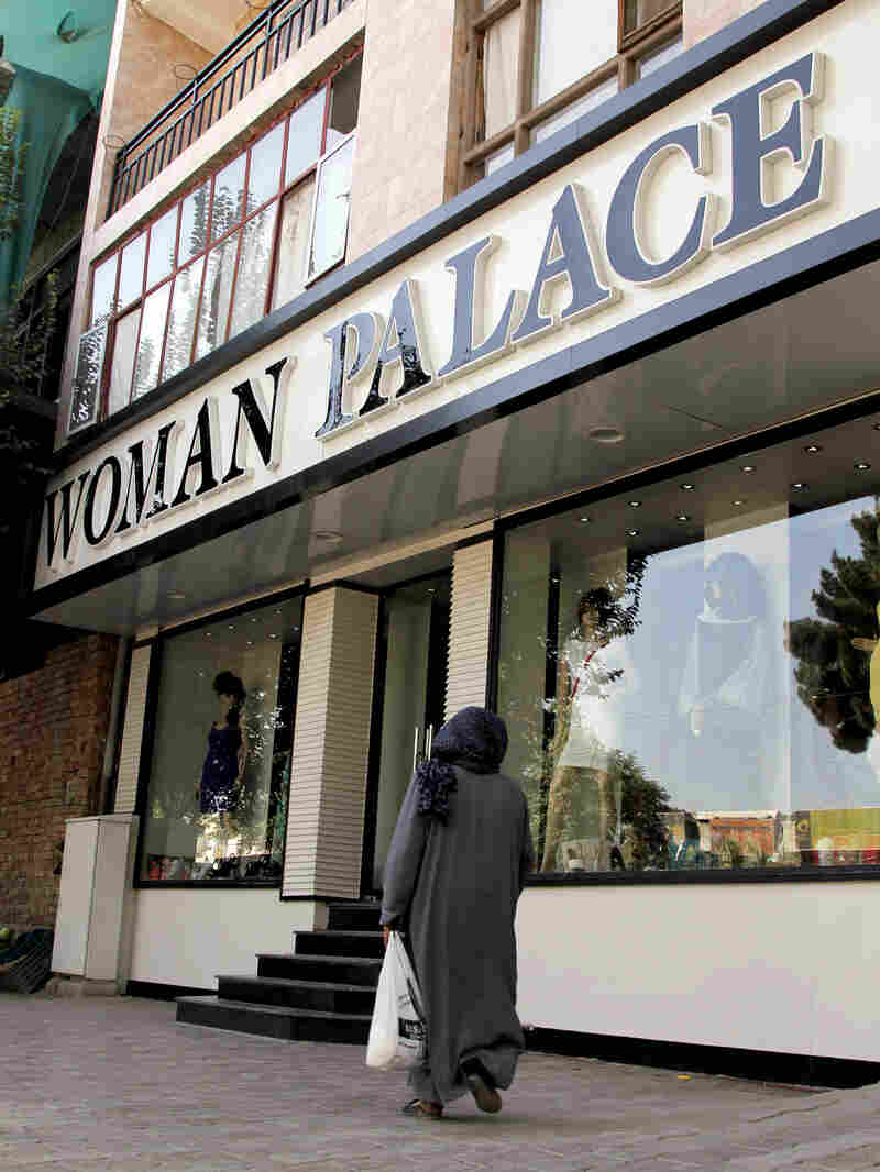 An Afghan woman walks past Woman Palace, which recently opened in Kabul. Despite the country's poverty and traditional, modest dress, stores catering to wedding gowns and other upscale women's clothing are doing a brisk business.