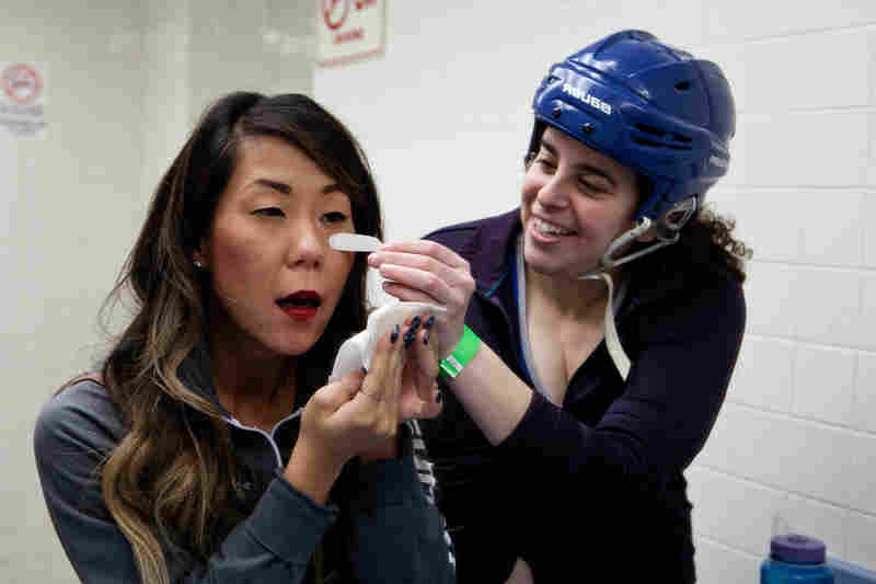 Kelli Cooper — aka Cooper Trooper (right) — applies a temporary tattoo on Nina Park, as they prepare for a roller derby bout at the Aleppo Shriners Auditorium in Wilmington, Mass.
