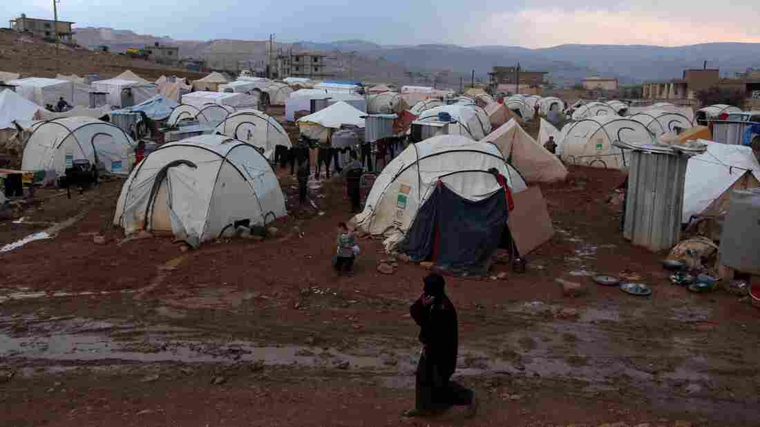 A Syrian refuge woman walks past tents at a refugee camp in the eastern Lebanese border town of Arsal, Lebanon, Monday, Nov. 18, 2013.