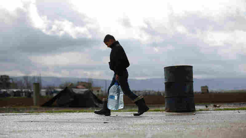 A Syrian refugee child carries water in the Fayda Camp, some 25 miles east of Beirut, Lebanon, on March 10.