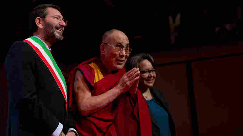 The Dalai Lama, flanked at left by Rome's Mayor Ignazio Marino, arrives at the opening of the World Summit of Nobel Peace Laureates in Rome on Friday.