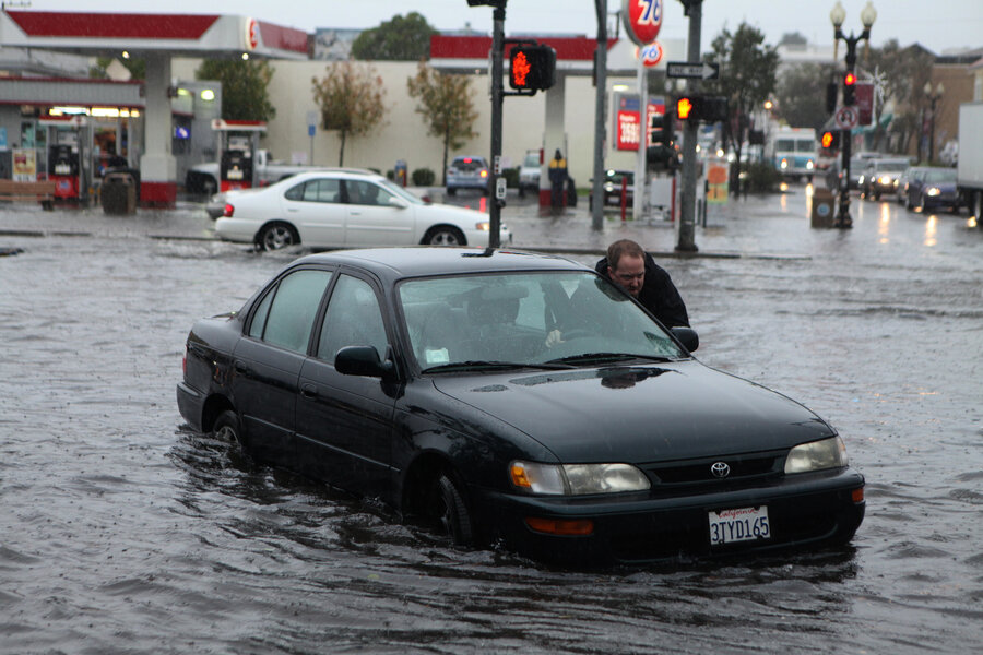 Mark Kunze of San Bruno pushes his stalled vehicle out of the flooded intersection in South San Francisco, on Thursday.