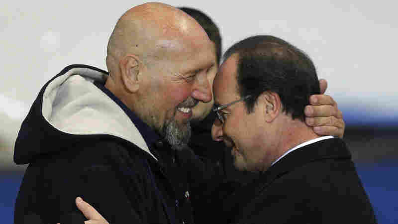 France's Serge Lazarevic (left) hugs French President Francois Hollande after arriving in France on Wednesday following his release.