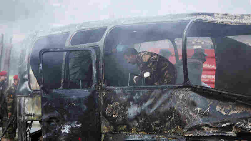 Afghan security personnel inspect a damaged bus at the site of a suicide attack in Kabul, Afghanistan, on Saturday. There was no immediate report of casualties, but the attack was one of several in the last 24 hours that have been blamed on the Taliban.