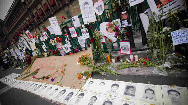 Flowers, candles and handwritten messages remembering the 43 missing students line the fence at the National Palace in Zocalo, Mexico City.