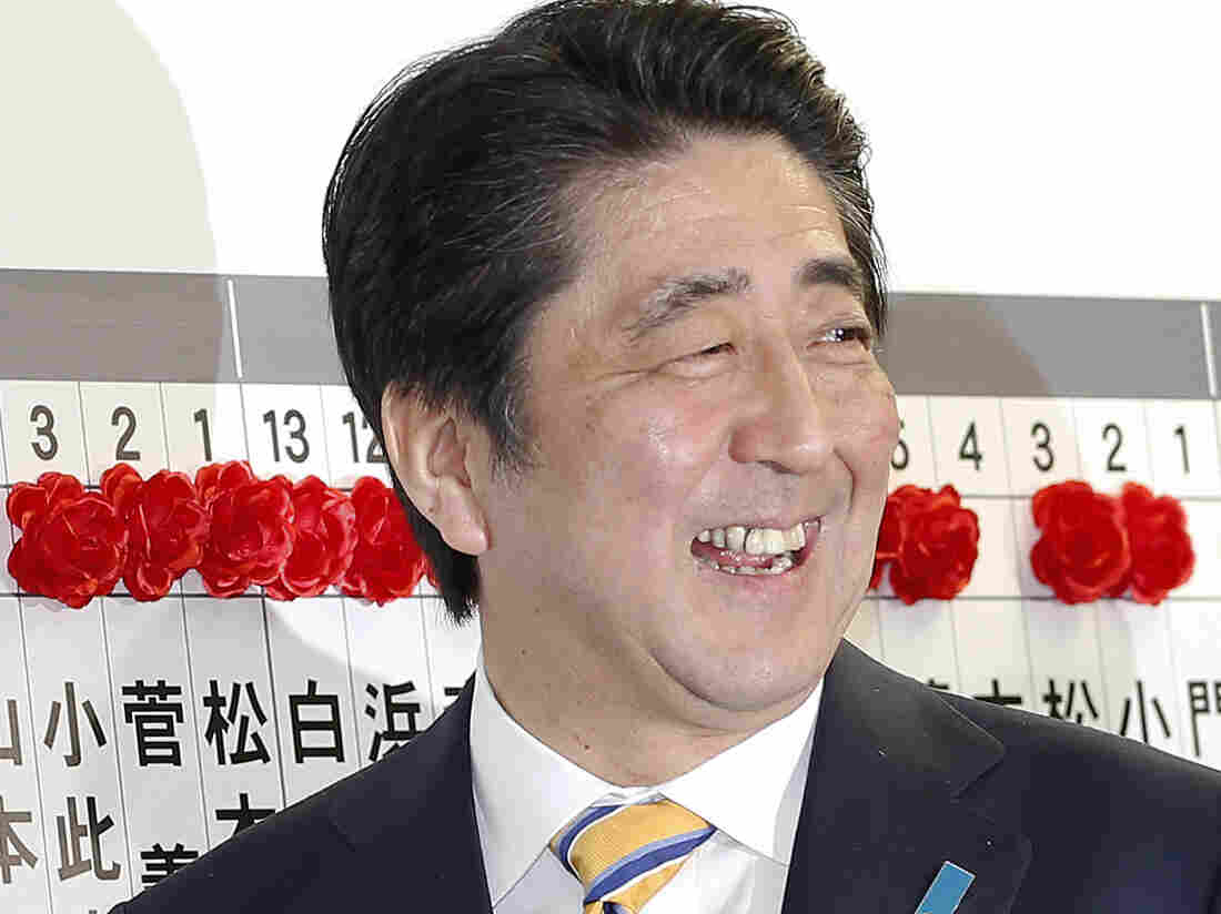 Japanese Prime Minister Shinzo Abe, leader of the Liberal Democratic Party, smiles as he places a red rosette on the name of his Liberal Democratic Party's winning candidate during ballot counting.