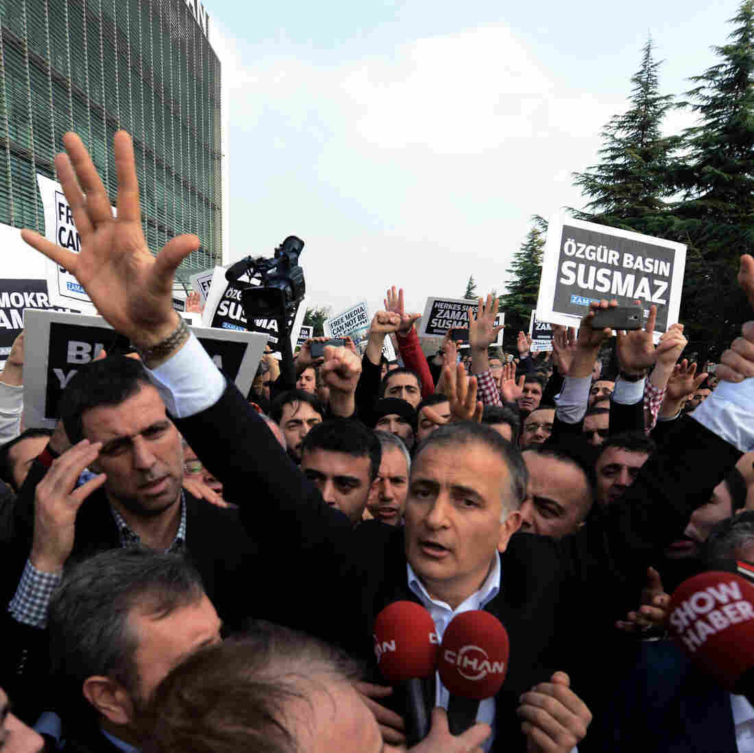 Ekrem Dumanli, editor-in-chief of Zaman, salutes cheering supporters as he is detained outside his office in Istanbul, on Sunday. Dumanli was one of two dozen people, including many journalists, detained in what is being described as a purge against anti-government figures.