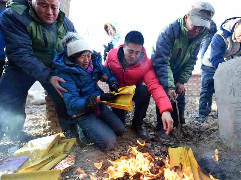 Shang Aiyun (second left) and Li Sanren (second right) mourn at the grave of their son, Huugjilt, in Hohhot, China. Huugjilt was executed in 1996 for the rape and murder of a woman in a public toilet. He was cleared of the crime on Monday.