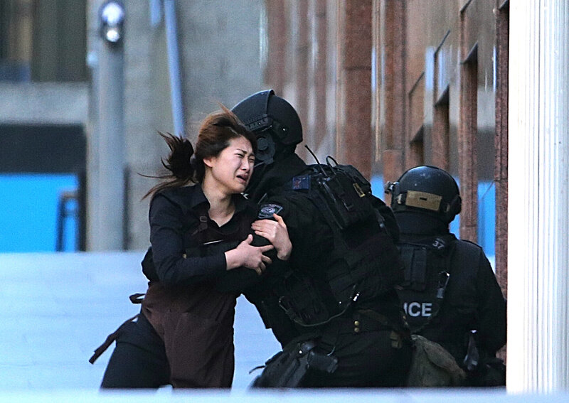 A hostage runs to armed tactical response police officers for safety after she escaped from a cafe under siege at Martin Place in the central business district of Sydney, Australia, on Monday.