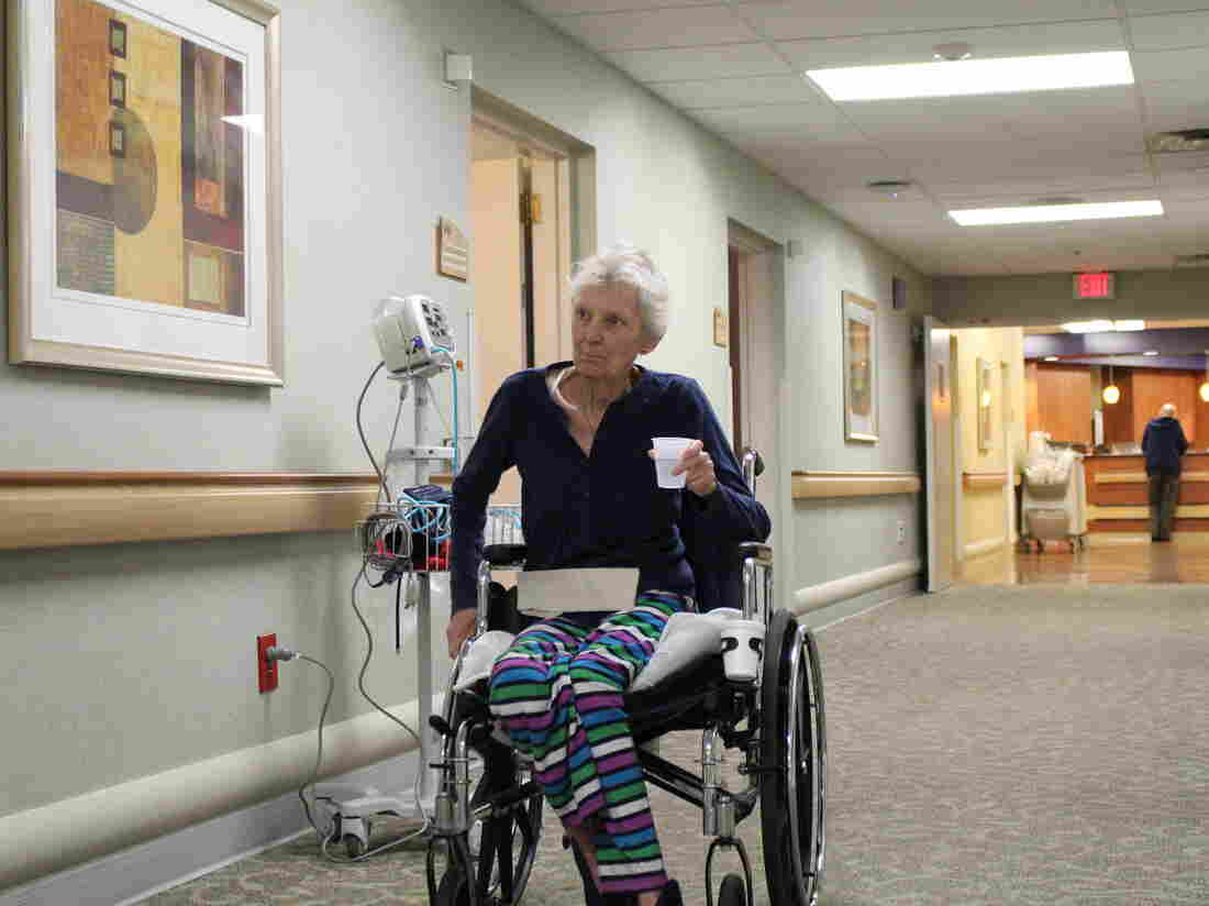 Donna Giron wheels through the halls of the nursing home she's lived in since May. Finding an affordable home of her own has been difficult.
