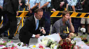Prime Minister Tony Abbott and his wife, Margie, pay their respects at the Martin Place memorial site on Tuesday in Sydney, Australia.