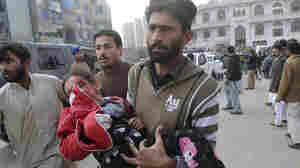 A Pakistani girl, who was injured in a Taliban attack on a school, is rushed to a hospital in Peshawar, Pakistan, on Tuesday.