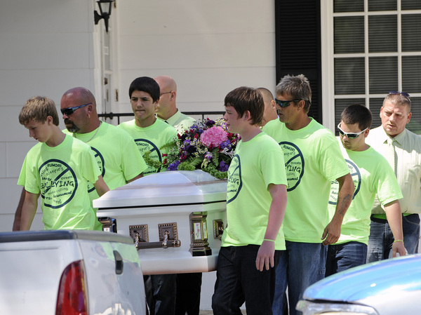 Pallbearers wearing anti-bullying T-shirts carry the casket of Rebecca Sedwick,12, to a waiting hearse in September 2013 as they exit the Whidden-McLean Funeral Home in Bartow, Fla.