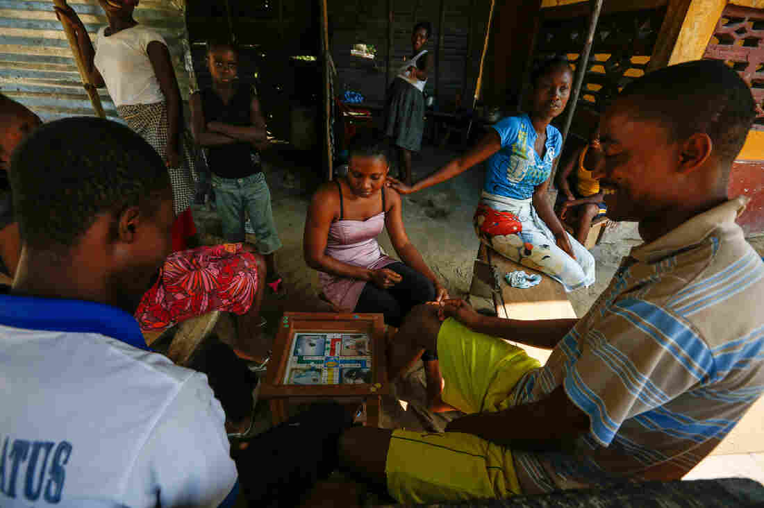 Residents of New Georgia Signboard, a small village just north of Monrovia, pass the time by playing a fast-paced board game called Ludo.